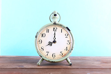 Alarm clock on wooden table on blue background