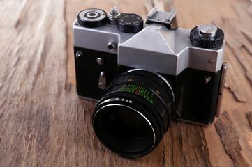Retro photo camera on wooden background