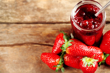 Jar of strawberry jam with berries on wooden background