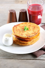 Stack of corn tortillas with stuffing and glass of juice