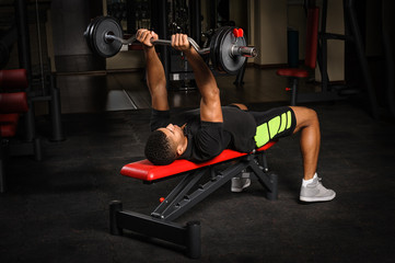 Young man doing arms bench french press workout in gym