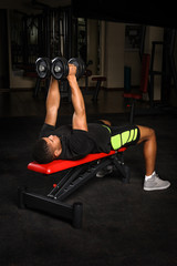 Young man doing arms bench flies workout in gym