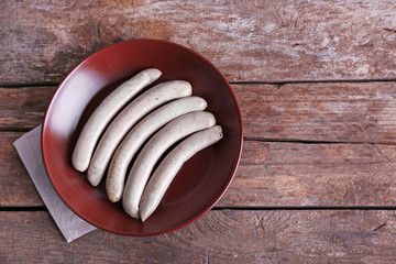 Cooked sausages on plate on wooden table background