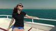 Young happy of life woman in sunglasses sits on a yacht bench of