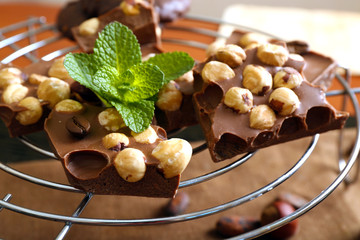 Chocolate with nuts and mint on metal stand, closeup