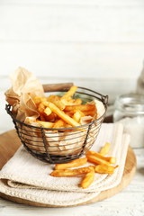 Tasty french fries in metal basket on color wooden background