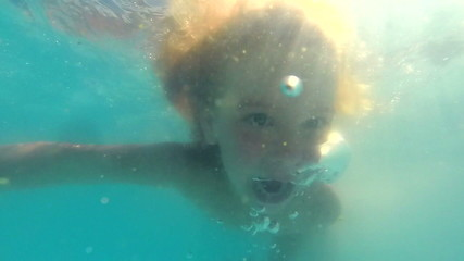Little girl dives underwater in a swimming pool