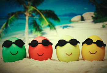 Four easter eggs with sunglasses on ocean beach – retro style