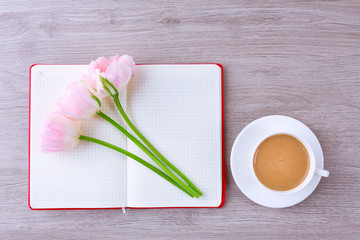 Beautiful tulips with diary and cup of coffee