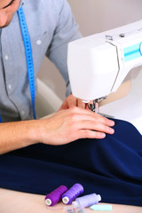 Man direct fabric in sewing machine
