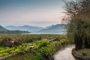 Bamboo bridge near reservoir with mountain and sky view