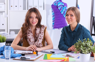 Two fashion designers working together at the desk
