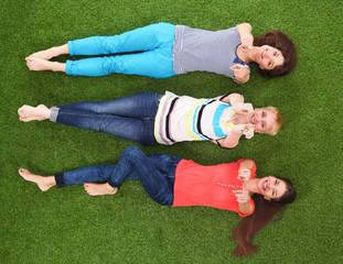 Young women lying on green grass