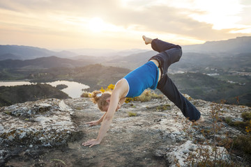 Young Caucasian woman performing yoga pose outdoors