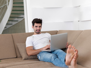 Man Relaxing On Sofa With Laptop