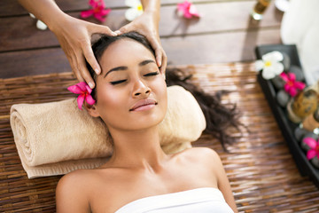 young beautiful Balinese woman receiving head massage