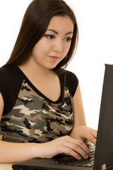 Asian American woman focused while typing on computer
