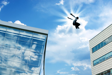 Silhouette of a Man Leaping off Building