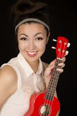 Beautiful teen girl holding a red ukulele smiling