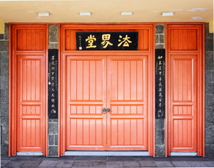 Red doors leading into a Buddhist temple located under the bronz