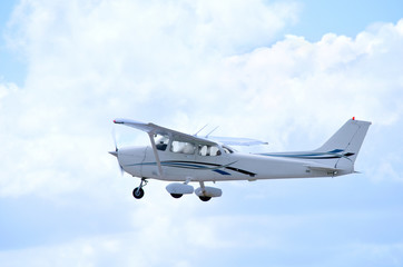Small private single engine airplane in flight with clouds