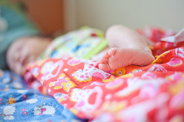 Tiny leg newborn baby in pink diapers