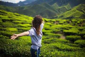 Freedom girl in mountains on tea plantation