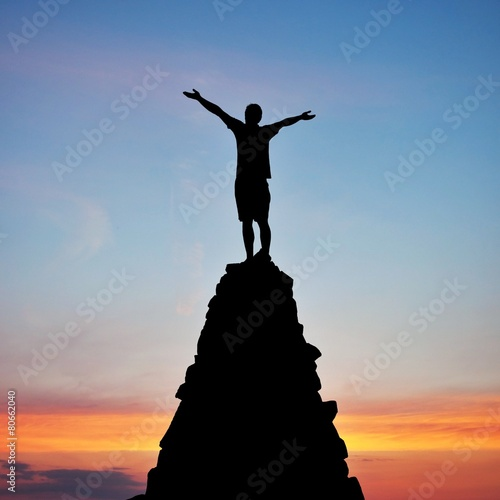 man on top of mountain in sunset