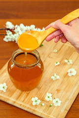 Hand holding wooden spoon with honey