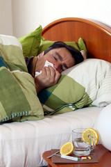 Mann, Fieber, im Bett, niest in Taschentuch,unwohl