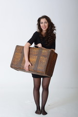 a brunette girl stands with antique suitcase on white background
