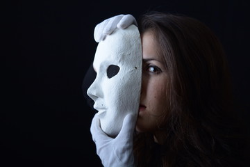 a brunette girl holding a white theatrical mask