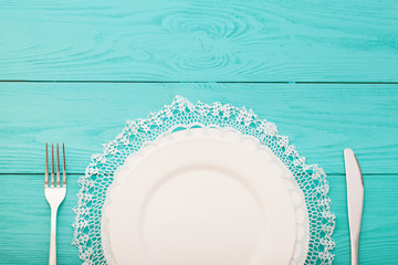 Cutlery and lace doily on wooden background