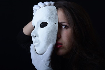 a brunette girl holding a white theatrical mask and cries