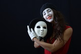 the girl is MIME holding a white mask and smiles