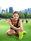 Woman doing stretching exercises on the green grass - 80665095