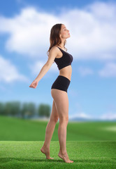 Young fitness girl standing on green grass