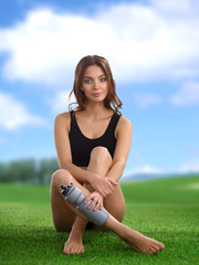 Young female athlete sitting on grass after exericise and