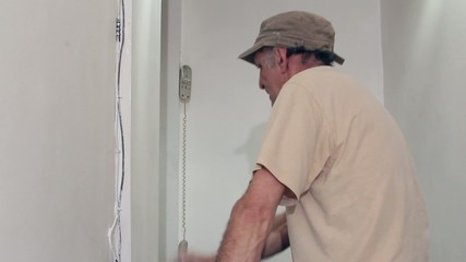 Worker painting with white paint