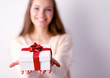 Young woman happy smile hold gift box in hands,standing over