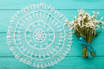 Round lace doily and flowers on wooden background