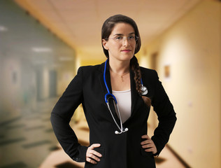 FEMALE DOCTOR WITH STETHOSCOPE AND GLASS INTO HOSPITAL CORRIDOR