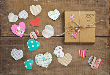 A gift on wooden background with hearts