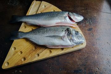 Pesci, orata e branzino crudi su tagliere in legno