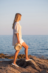 Woman standing on rock and looking at sea