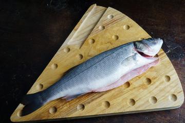 Pesce, branzino crudo su tagliere in legno