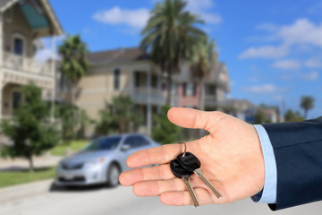 Cropped image of estate agent giving house keys  near with a vil