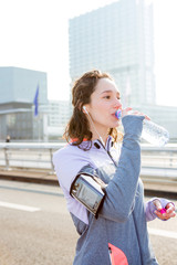 Woman drinking water during a running session