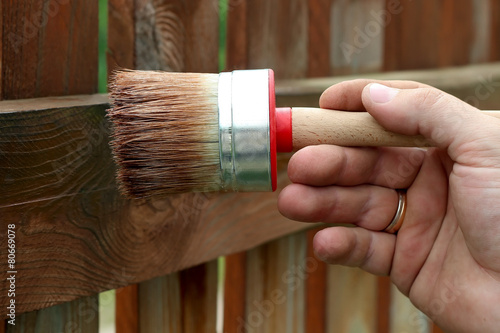 Applying protective varnish to a wooden fence - 80669078