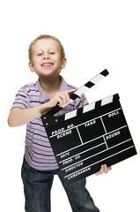 boy with clapperboard grinning